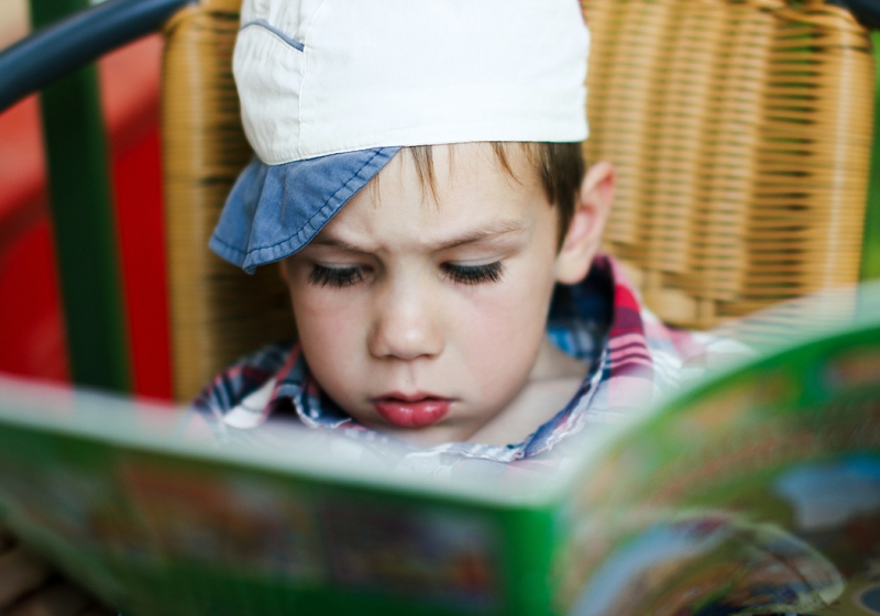 boy intently reading a children's magazine